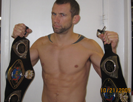 REPUBLIC Coach Dave Nielsen holding IKF California Muay Thai Championship Belt and IKF West Coast Muay Thai regional Championship Belt