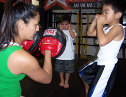 Coach Gina holding muay thai mitts for kids mixed martial arts class.