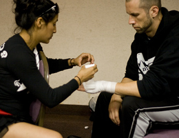 Coach Gina Reyes wraps Coach Dave Nielsen's hands pre fight for WCK World Championship Muay Thai at Hollywood Park Casino.